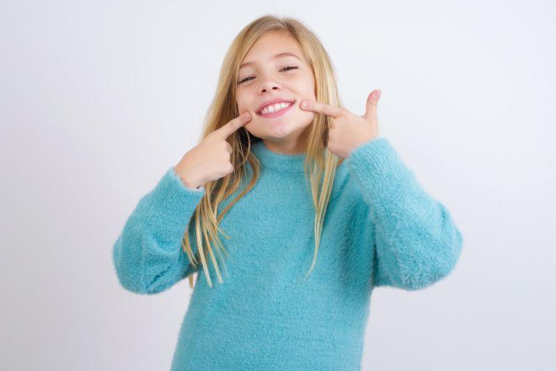 Girl pointing at her own straightened smile, after braces